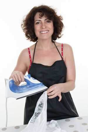 atomiser: Woman ironing clothes on ironing board, close-up, on light background