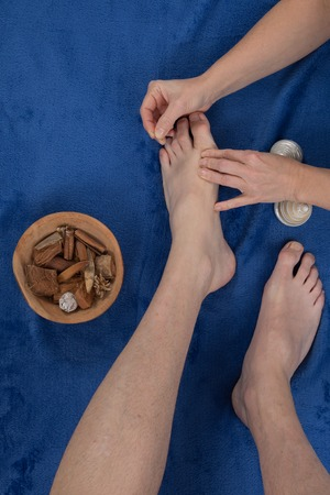 diagnosing: A patient receives a foot acupuncture Stock Photo
