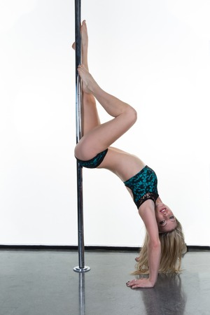 pole dancer: One caucasian woman pole dancer dancing in  studio isolated on white background Stock Photo