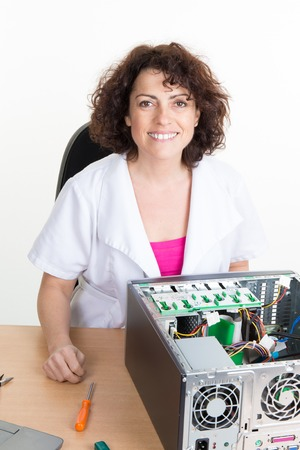 technically: Smiling woman fixing computer on a white background