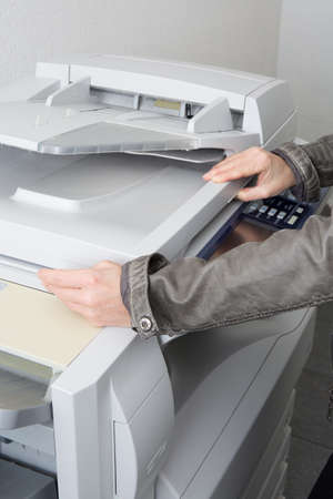 mfp: Woman hand using copy print machine at business place
