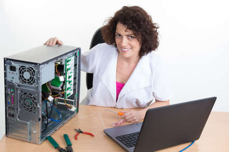 edv: Woman fixing a computer hard drive at business place Stock Photo