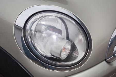 burnished: Closeup of a grey car headlight Stock Photo