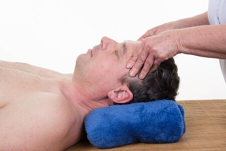 complementary therapies: Female sports massage therapist holding male clients head and massaging tight neck muscles with finger and thumbs