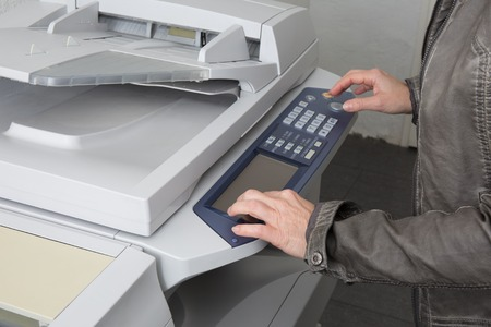 mfp: Womans hand with a working copier at work