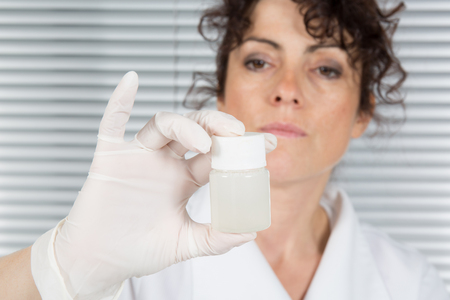 attentively: Scientist female looking attentively at sample