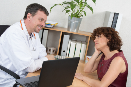 fedup: Serious doctor listening to patient explaining her painful in his office Stock Photo