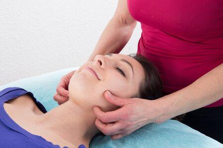 esthetics: Beauty woman having cosmetic massage, facial treatment, close up. Stock Photo