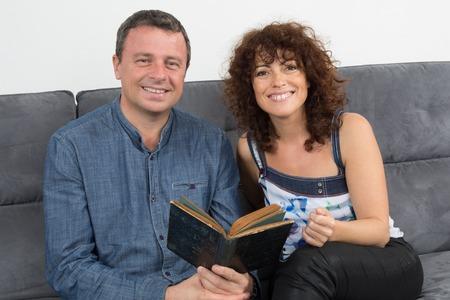 donna innamorata: coppia di mezza et� che si distende in divano di casa libro di lettura Archivio Fotografico