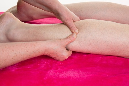 A physio gives myotherapy using trigger points on athlete man