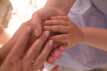 senescence: hand of old woman and young woman and child