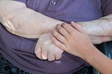 80 year old: Old and young. Childs hand on arm of a mature woman