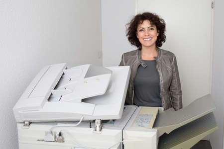 copy machine: Portrait of smiling businesswoman using copy machine in office Stock Photo