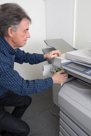 photocopy: Frustrated man opening photocopy machine in office trying to fix problem Stock Photo