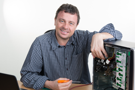 computer device: Computer engineer working on broken console smiling at camera in his office Stock Photo
