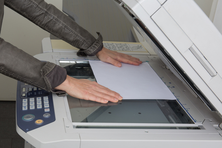 mfp: Womans hand with working copier at work