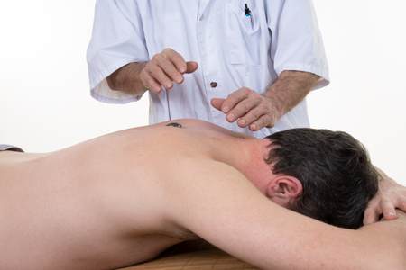reiki: Mature man lying on his back, gets massage,reiki,acupressure on his face, focus on face and hands
