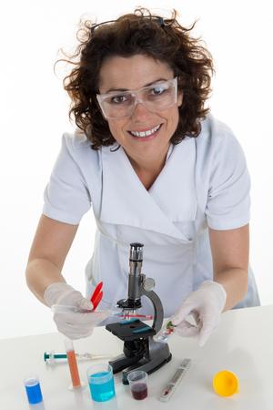 personas enfermas: Cient�fico sonriente mujer joven con microscopio y mirando a la c�mara mientras se trabaja en el laboratorio