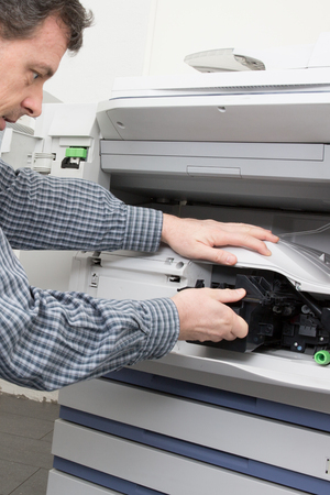 fotocopiadora: Shot male technician repairing digital photocopier machine