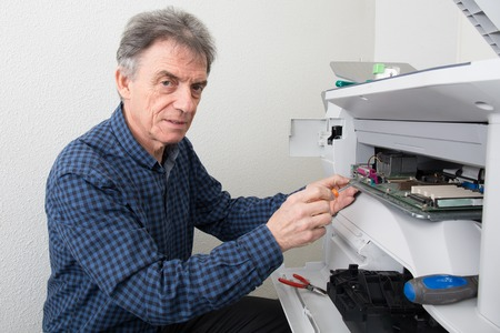 ordinateur de bureau: Handyman fixant l'imprimante de bureau au bureau d'affaires