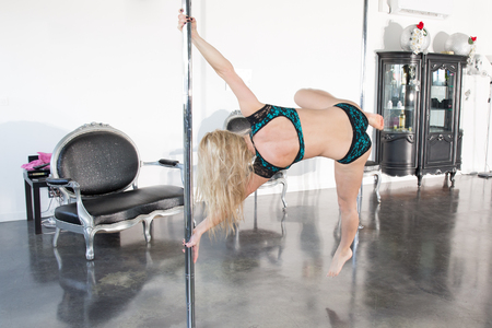 striptease women: Beautiful dancer on the pole at fitness class isolated Stock Photo
