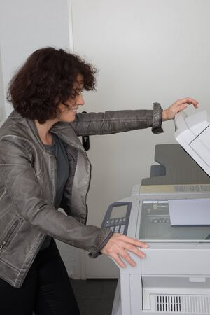 copy machine: Caucasian office woman lifting up lid of copy machine at work