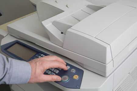 photocopy: Business man with his finger on the start key and ready to make a photocopy Stock Photo