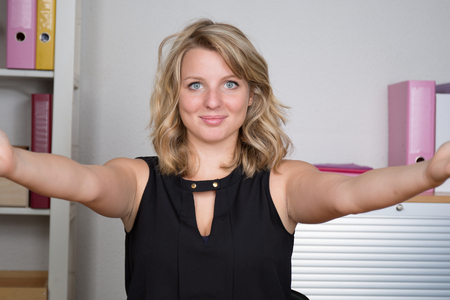 youthful: Selfie time. Pretty youthful smiling blond-haired woman sitting in armchair at office