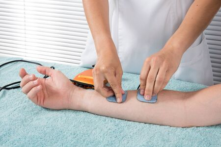 electrophoresis: Physical therapist positioning  electrodes on lower arm Stock Photo