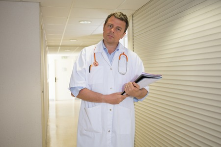 white person: Male doctor holding reading patient`s card -next to  the wall at hospital.