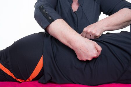 lumbar curve: Masseur massaging the back of a man in a room Stock Photo
