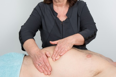healing practitioners: Macro close up of Osteopathic belly massage. Stock Photo