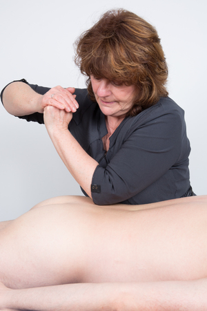 healing practitioners: Close up of therapist applying pressure on male back with elbow.