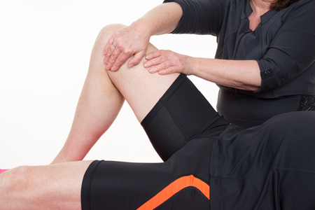 kneecap: Practitioner female using his fingers to massage a knee in a room Stock Photo