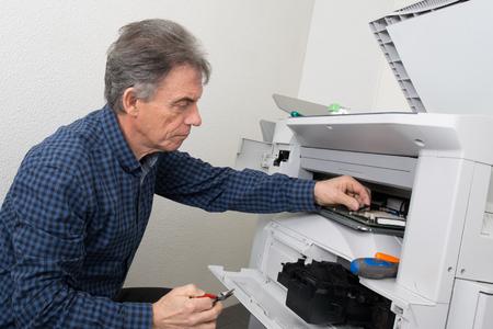 fotocopiadora: disparó de cerca joven técnico masculina máquina fotocopiadora digital de reparación