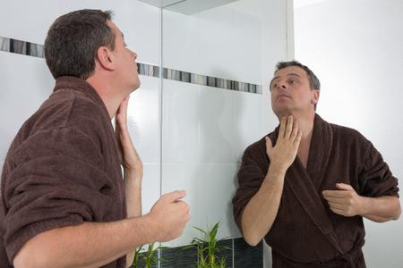 therapeutics: Happy man in bathrobe looking at the mirror Stock Photo