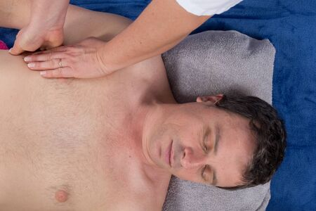 therapeutical: Man lying on his back in a spa having a shoulder massage