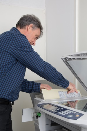 photocopy: Mature businessman fixing cartridge in photocopy machine at work