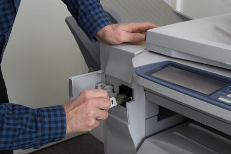 printer cartridge: Man takes out black cartridge from white printer at work