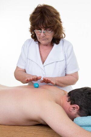 reiki: Massage therapist performing Reiki over man at health spa