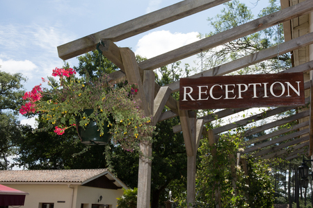 revive: Hotel Reception direction sign on wooden background, blue sky Stock Photo