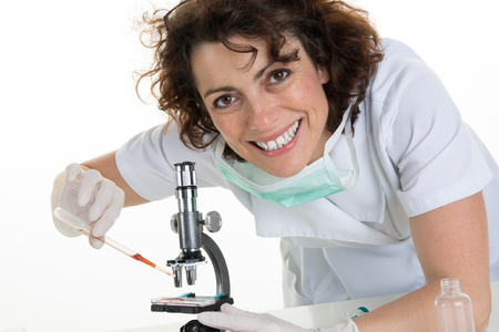 researchers: Portrait of a smiling female with researchers working on experiments in the laboratory Stock Photo