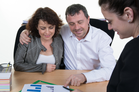 young  family: Happy and smiling couple signing financial contract