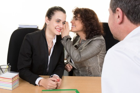 managerial: View over the shoulder of a  female applicant of two personnel managers conducting a job interview whispering amongst themselves about their impression and decision