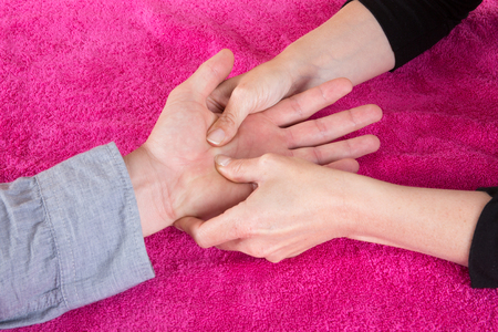 psychic reading: Reading the lines hand and womans hands on pink