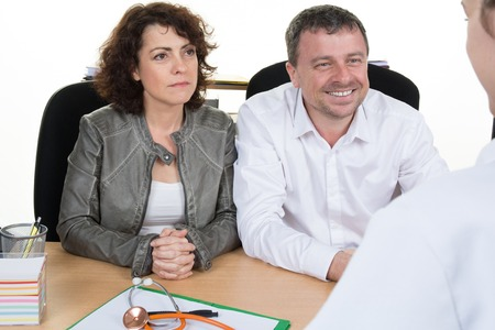 two people with others: Couple in discussion with doctor in IVF clinic sitting at desk