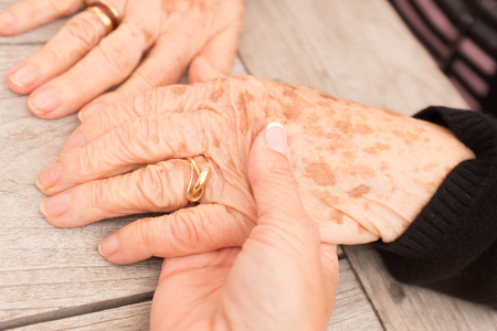 elderly care: Hands of an elderly woman with freckles holding the hand of a younger woman. Stock Photo