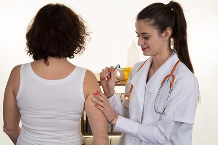 Vrouwelijke arts geeft een intramusculaire injectie in de vrouwelijke arm
