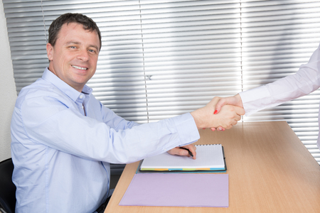 deal in: Smiling business man shaking hands after a deal in office Stock Photo