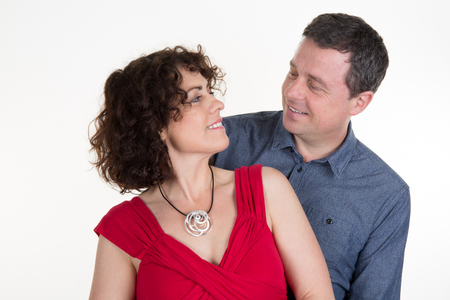 playfulness: Picture of happy couple looking at each other isolated on white background.